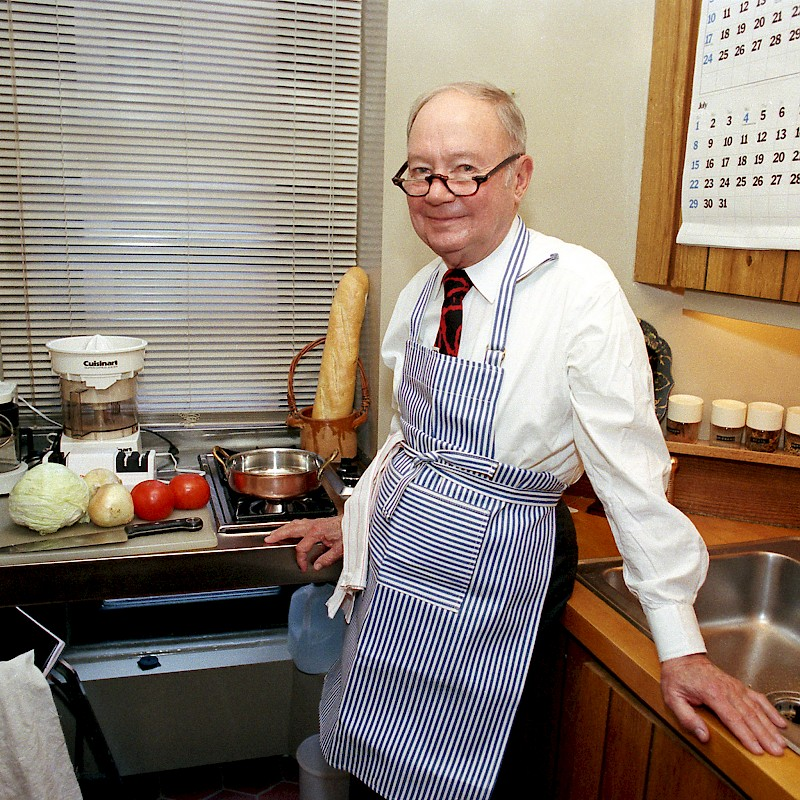 Craig Claiborne, prolific food critic for the <i>New York Times</i>, poses in his kitchen with a baguette in the background.