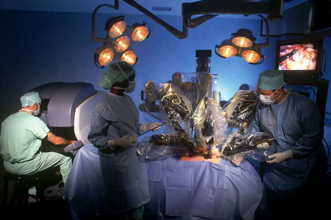 The many arms of a da Vinci robot perform surgery in a theatrically-lit operation room.