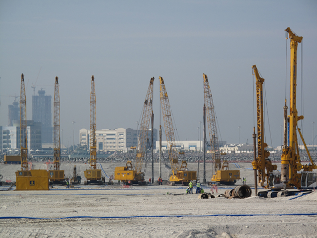 Cranes align on the construction site of the Louvre Museum, Abu Dhabi. The museum, among other construction sites in Saadiyat Island like the Guggenheim Museum, has been criticized for using precarious immigrant labor.