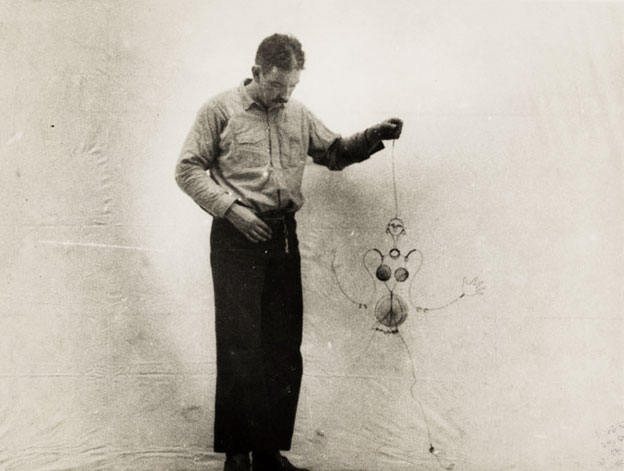 Alexander Calder animates a Josephine Baker puppet of his own construction. The puppet caricature is sexualized by the inclusion of extra wiggling metal pieces representing her breasts and torso.