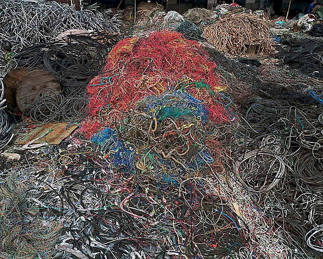 Edward Burtynsky, <em> China Recycling #7, Wire Yard, Wenxi, Zhejiang Province,</em> 2004. E-waste appears as a mass of colored wires dumped on the ground in rural China. The composition uses color to create a visual pattern pleasing to the eye but disturbing to the soul. See www.edwardburtynsky.com